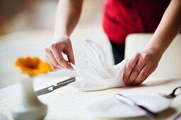 A waitress folding a napkin