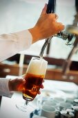 A waitress pouring draught beer