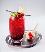 Fruit cocktail with raspberries and mint on a silver tray