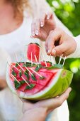 Guests at a garden party eating watermelon on sticks
