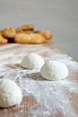 Balls of bread dough on a floured wooden board