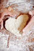 Hands shaping heart-shaped bread