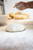 A baker scattering flour over bread dough