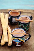 Mexican hot chocolate with cinnamon sticks and churros
