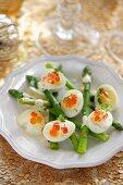 Quail's eggs with salmon caviar on green asparagus