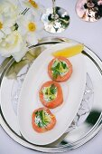 Smoked salmon rolls filled with goat's cream cheese and dill on a table laid for a party