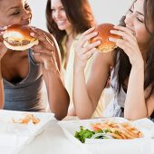 Friends eating take-out hamburgers and french fries