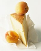 A slice of mountain cheese and two apricots