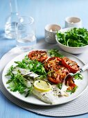 Baked sea bass with tomatoes and rocket