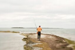 Man Riding Bicycle With Fishing Rods on Beach, Florida Keys, USA