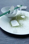 An oriental place setting and chopsticks with a teabag print in green tea powder