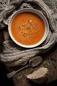 A bowl of tomato soup sprinkled with basil leaves with a knitted scarf, spoon and a slice of bread.