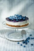 Fresh blueberry cheesecake on a cake stand with a cake slicer and a plate