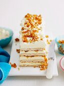 A layered ice cream cake with a biscuit base, cream and almond brittle