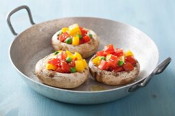 Mushrooms stuffed with tomatoes, yellow peppers and peas
