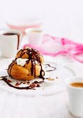 A profiterole with cream, chocolate sauce and almonds