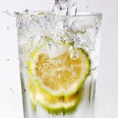 Water being poured into a glass of lime slices