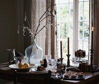 Zweig mit Glasanhängern in Ballonflasche auf weihnachtlich gedecktem Tisch