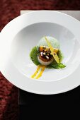 A fried scallop with vegetables rolls in stinging nettle sauce