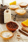A jar of homemade mincemeat, mince pies on a rack, spices and half an orange