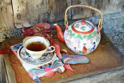 Vintage teacup, saucer and Chinese china teapot on rusty tray decorated with Virginia creeper leaves