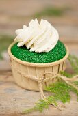 A green cupcake decorated with buttercream
