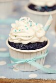 A chocolate cupcake decorated with buttercream and blue sugar pearls