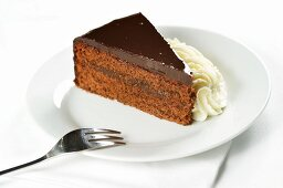 Slice of Sacher torte with whipped cream