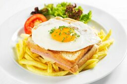 A toasted ham and cheese sandwich topped with a fried egg on a bed of chips