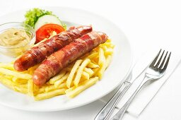 Grilled sausages wrapped in bacon with mustard and chips