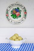 Potato dumplings in a round terrine underneath an old-fashioned painted plate hanging on a wall