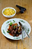 Venison goulash with mushrooms and Spätzle (soft egg noodles from Swabia) next to a pistol