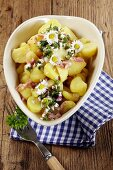 Warm potato salad with bacon and daisies