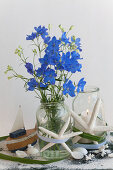 Bouquet of larkspur and candle lantern decorated with beachcombing finds