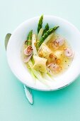 Asparagus broth with dumplings and onion rings