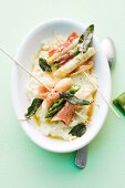 Asparagus skewers with ham and sage on a bed of creamy risotto