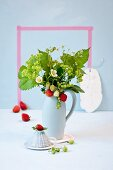 Pale blue jug of fresh strawberries, strawberry flowers and lady's mantle