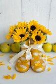 Sonnenblumen in Gummistiefeln vor einer Reihe Quitten