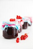 Jars of redcurrant jam with fabric covered lids