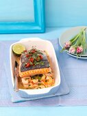 Baked salmon with prawns, chilli peppers and spring onions