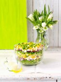 A layered salad with peas, red onions, egg, smoked bacon, lettuce and cheddar cheese
