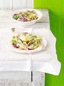 A mixed leaf salad with apple, radishes and poached egg