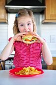 A little girl eating a hamburger and fries