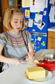 A girl in a kitchen cutting a piece of butter