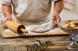 A confectioner rolling out biscuit dough
