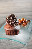 A chocolate cupcake decorated with sugar pearls and gold leaf