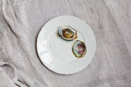 Two oyster shells on a porcelain plate, one with a pearl in