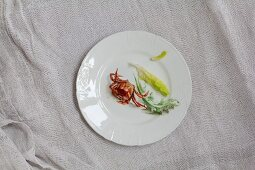 A red crab and various lettuce leaves on a white porcelain plate