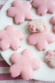 Flower-shaped biscuits with pink icing on plate