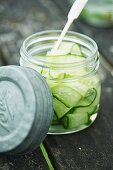 A jar of cucumber salad on a picnic table